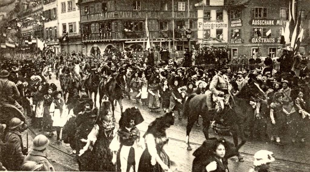 1918  Un Général et son Etat-Major escortés par de jeunes Alsaciennes en costume régional